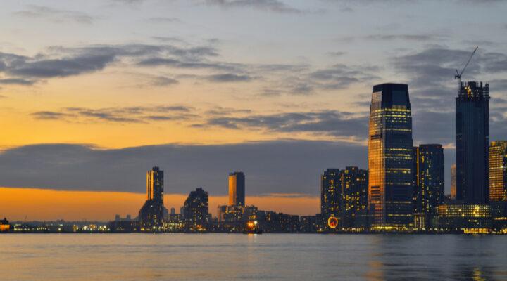 Header image of the evening skyline of Jersey City.
