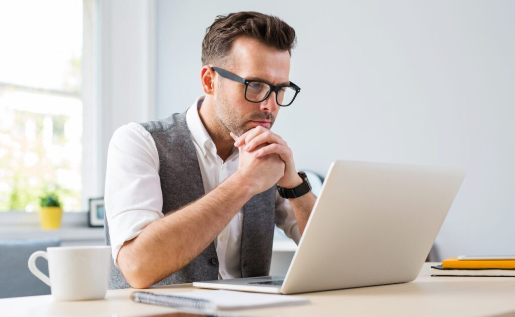 A man sits thinking in front of his laptop computer.