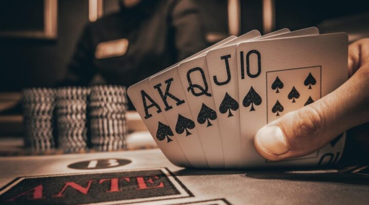 Close-up of a player's perspective showing a royal flush at a poker table, with casino chips in the background.