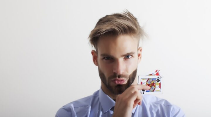 Young businessman holding a pair of cards against a white background.