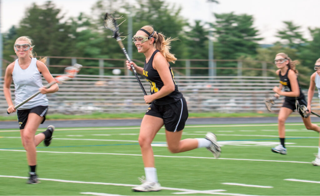 Opposing teams run across a playing field during a girls' lacrosse game.