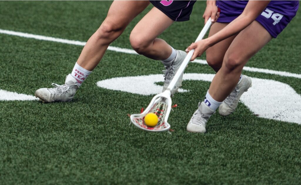 A lacrosse player on a field scoops the ball from an opponent and carries it forward.