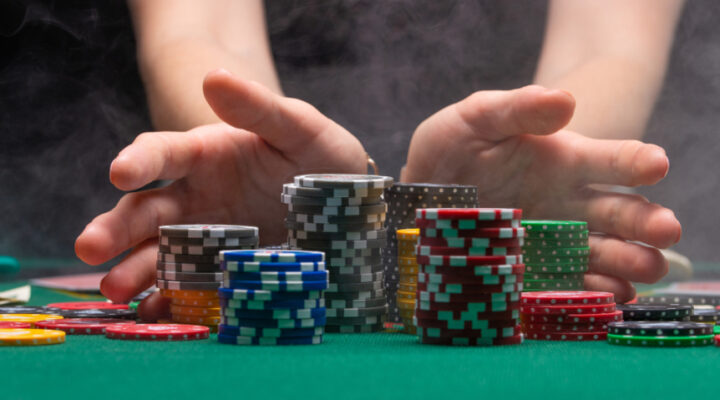 Hands moving casino chips towards a winner.