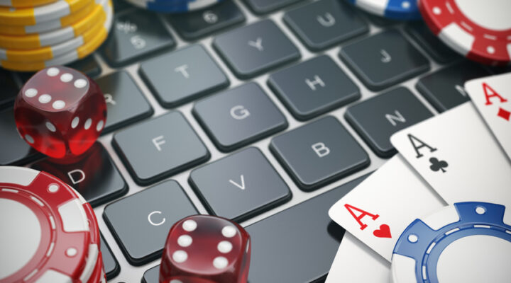 Dice and cards lying on top of a computer keyboard.
