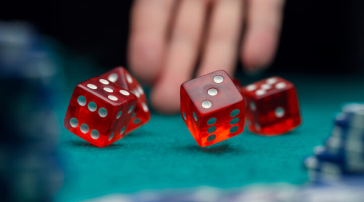 Red dice bouncing onto a casino table.
