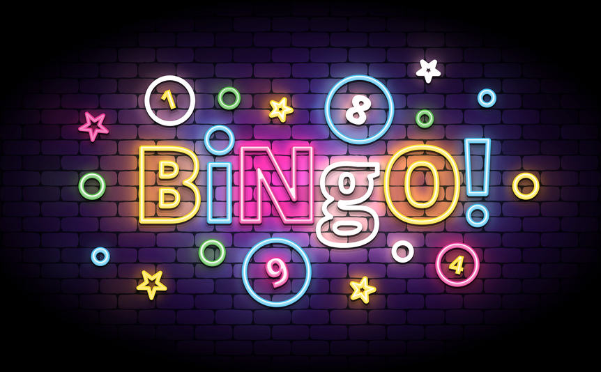 The world 'bingo!' spelled out in lights against a brick wall.