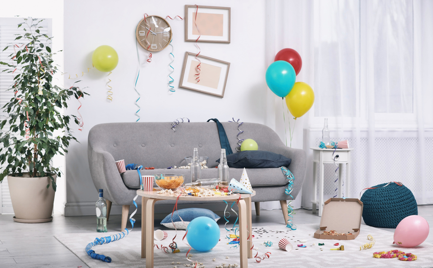 Snacks, drinking cups, and streamers left on a gray couch after a party.