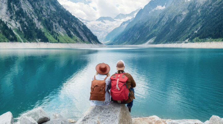 A couple with backpacks and hats sit in front of a lake.