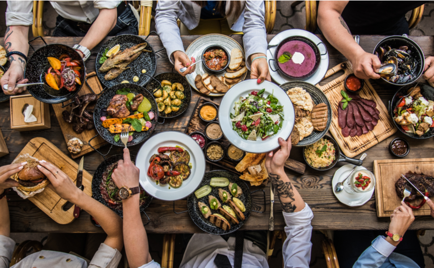 A top view of a table laden with food that has mostly been grilled.