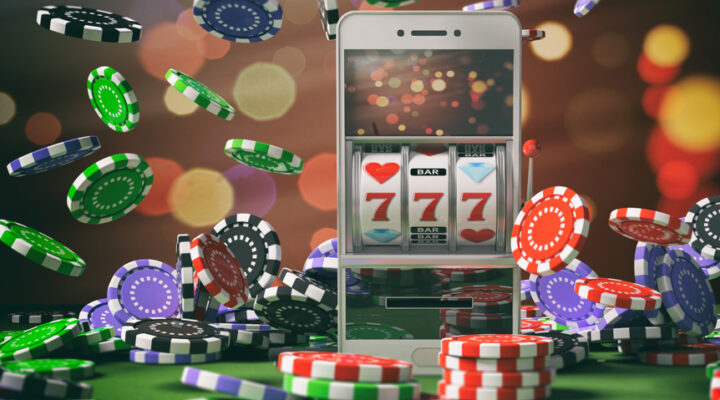 A slots reel on a mobile phone surrounded by casino chips.