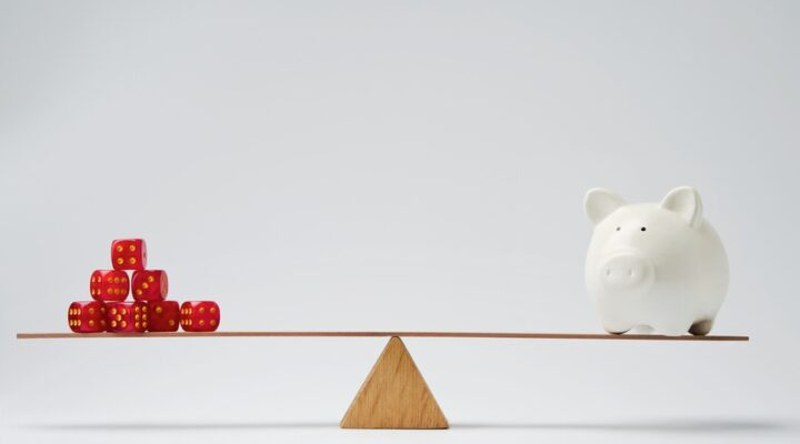 Balanced wooden seesaw with dice on one side and a piggy bank on the other against a white background.