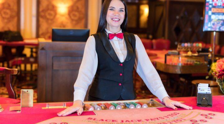 A friendly female casino dealer smiles.