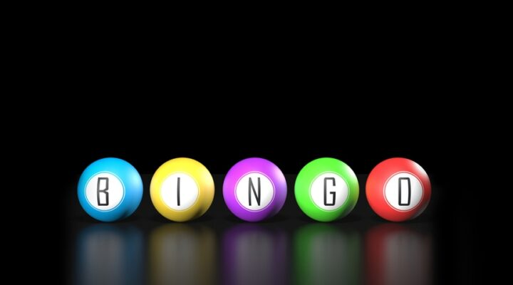Colorful bingo balls spelling out the word bingo on a reflective black surface