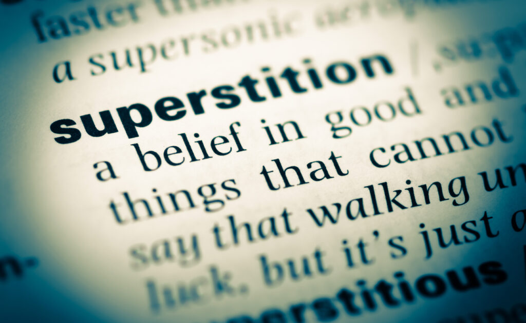 The words superstition highlighted in a dictionary.