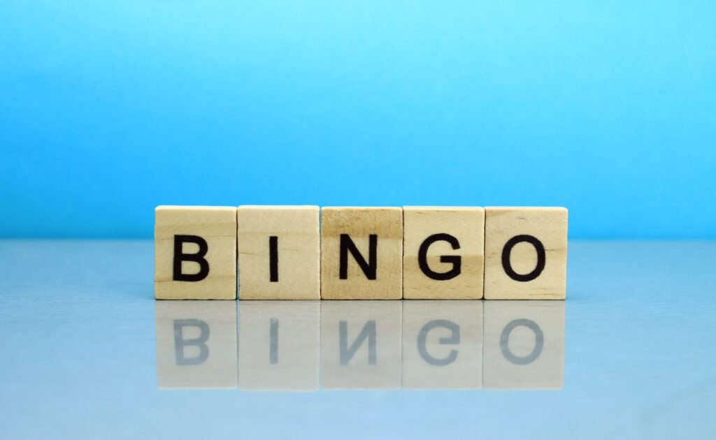 Wooden blocks spelling out the word bingo on a reflective surface with a blue background.