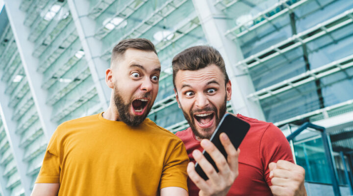 Two excited men looking at a phone shouting and celebrating.