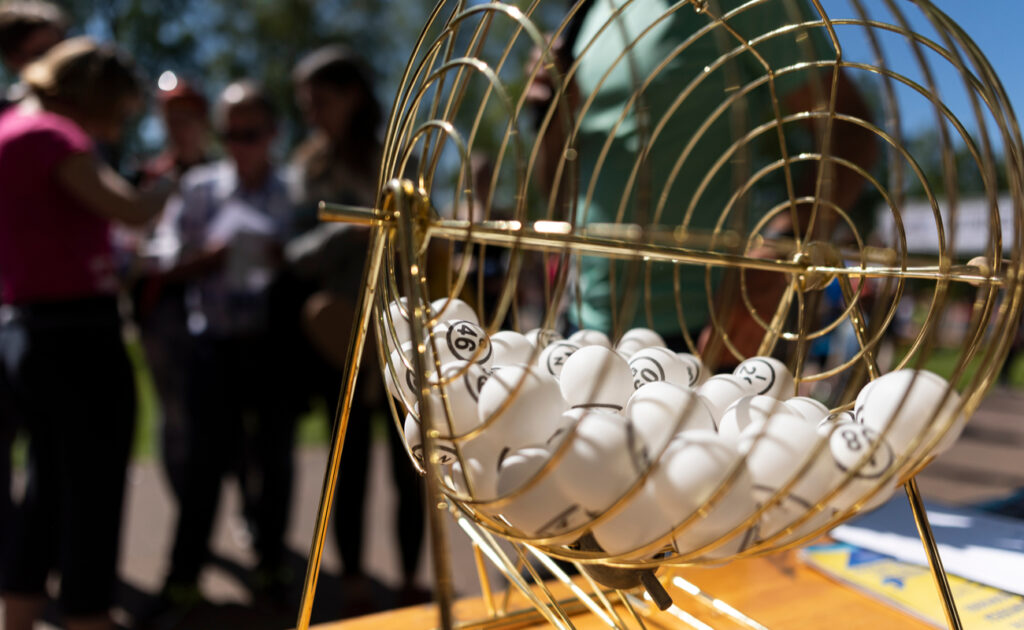White bingo balls in a gold cage on a table outside.