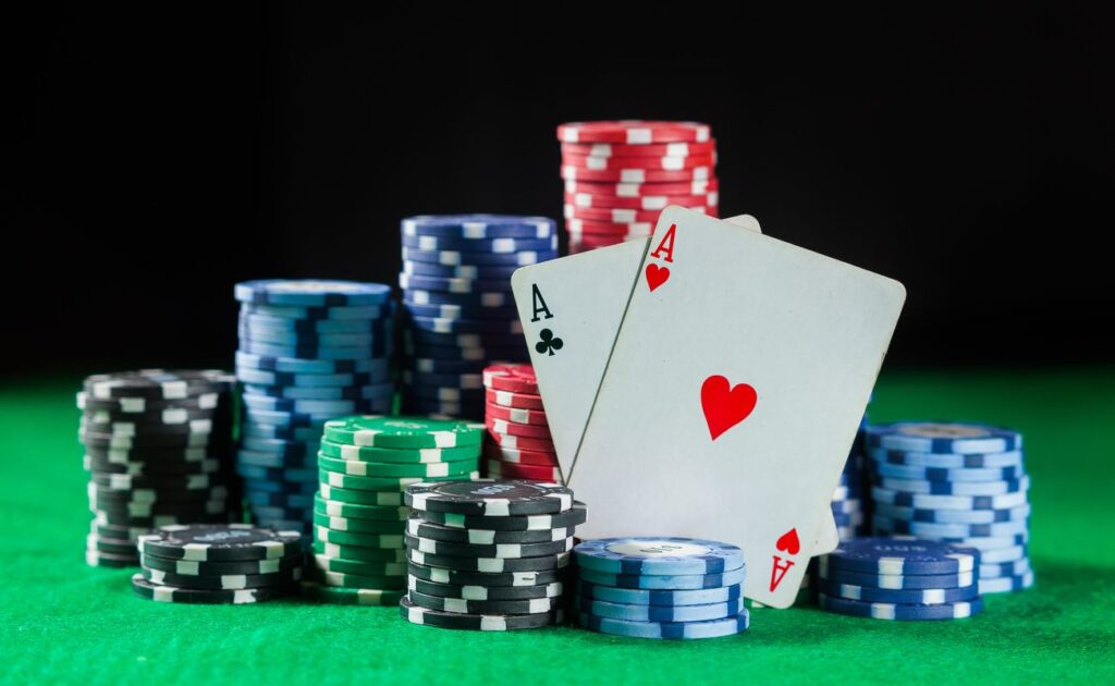 Poker chips and cards on a green felt table.