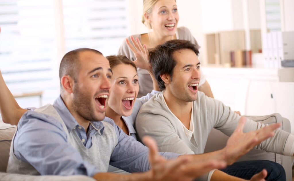 Four people react to something on their TV.