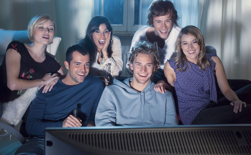 A group of friends watches TV together.
