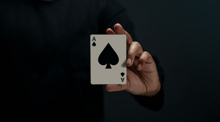A hand holding a playing card.