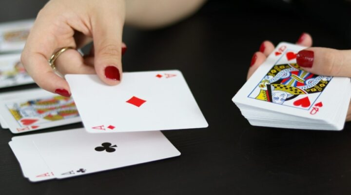 A woman arranging playing cards on a black table.