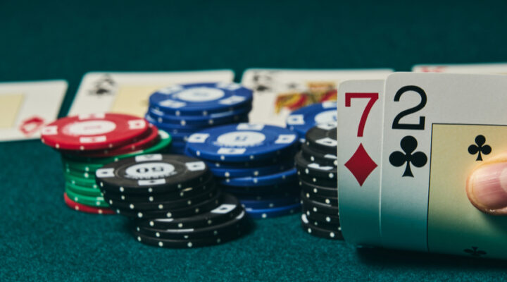 Some poker chips in the background with 7 and 2 cards in the foreground.
