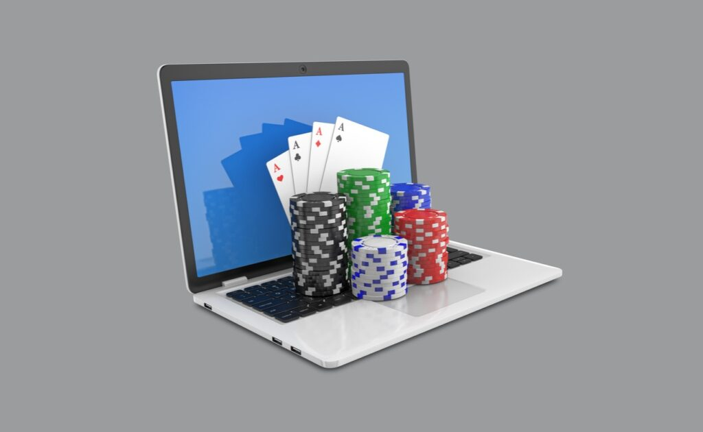 Casino chips and playing cards on top of an open laptop against a gray background.