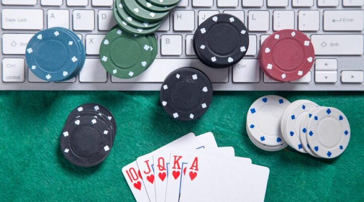 Computer keyboard on a green felt table with casino chips and playing cards around and on top of it.