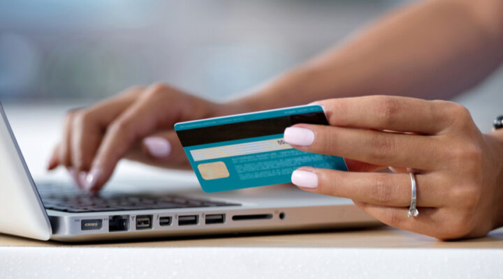 A woman holding a blue bank card typing on a laptop keyboard.