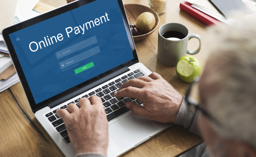 """A person sits with their hands on a laptop keyboard, with writing on the screen saying """"Online Payment."""""""