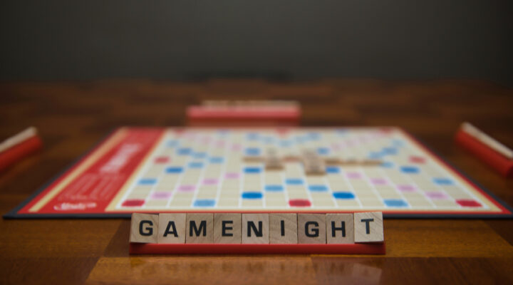 """Letter tiles spelling out the words """"game night"""" on the stand in the foreground with a game board in the background."""
