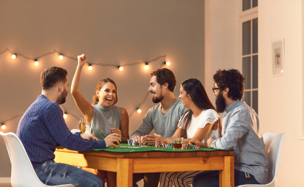 A group of friends sitting around a table with a board game and one woman with her hand in the air.