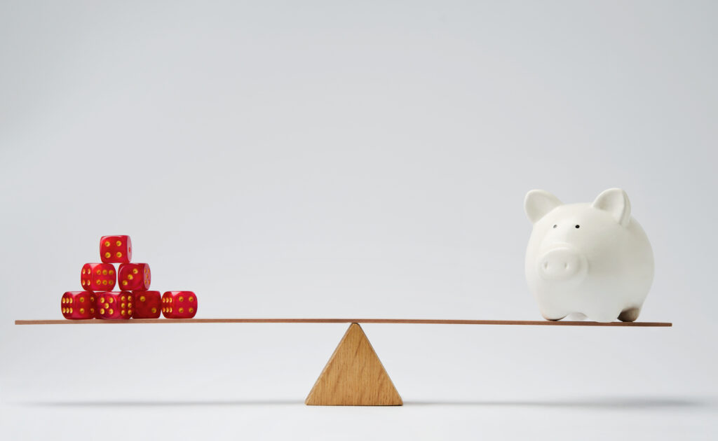 A white piggy bank balances on one side of a scale with red dice on the other side.