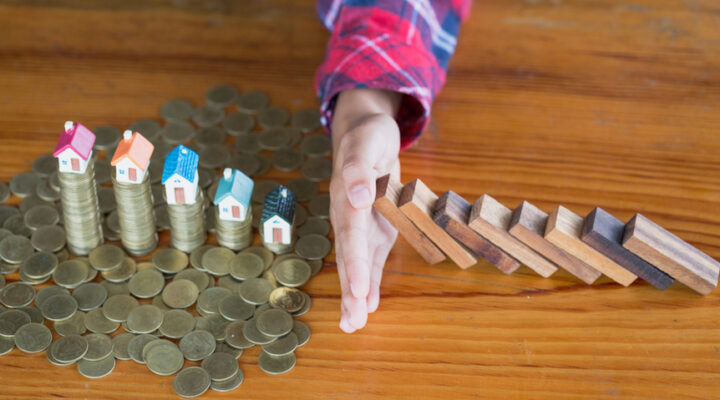 A hand stops a stack of dominoes from knocking over coins with houses on them.