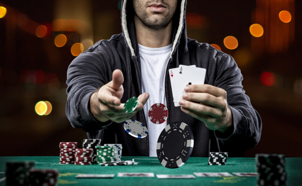 A player in a hoodie shows two aces and throws poker chips into the center of a table.