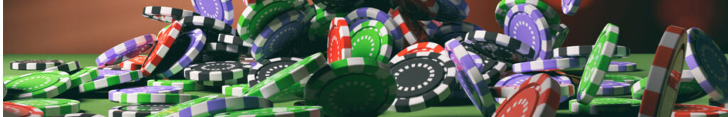 Poker chips fall onto a green table.