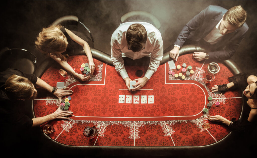 Players at a red poker table seen from above.