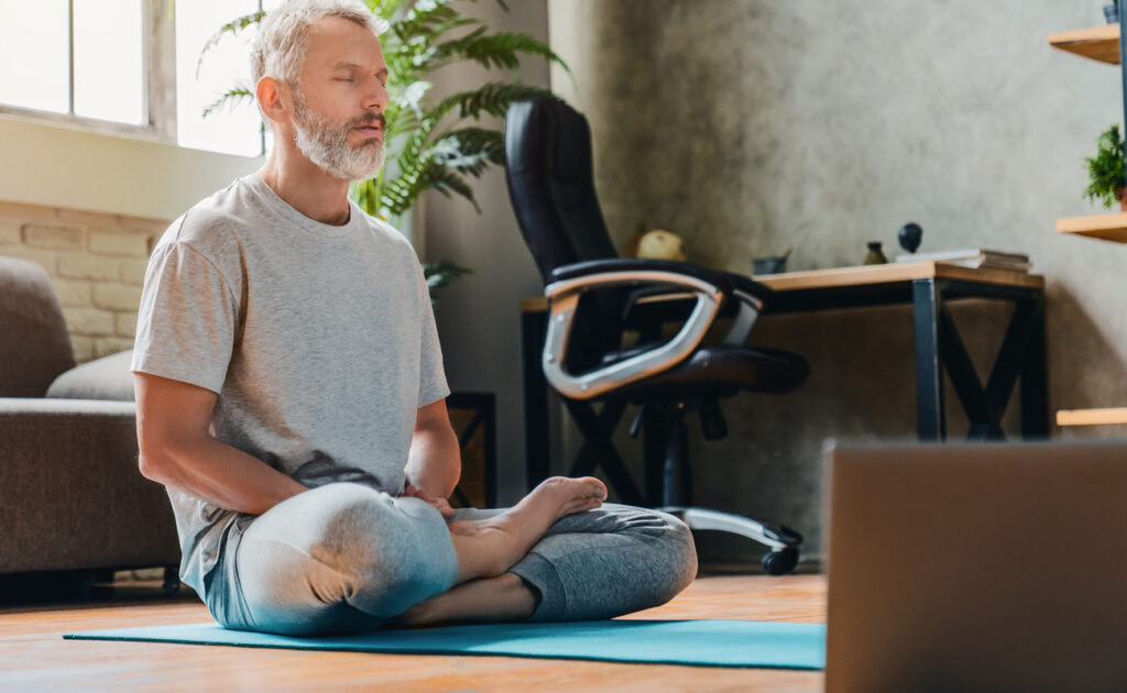A man meditating in his home office.