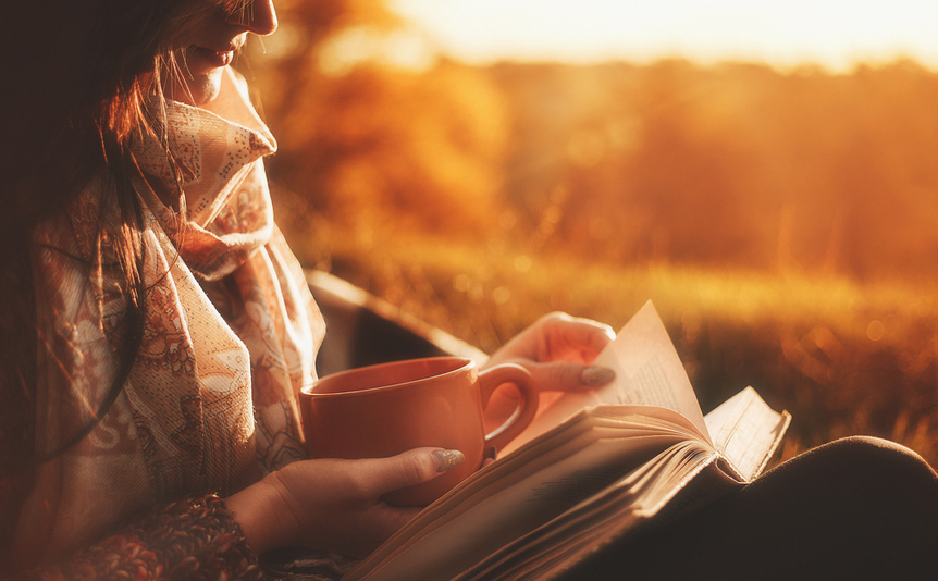 Woman reading a book and holding a cup.