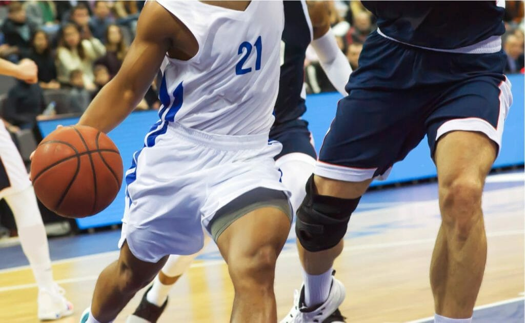Two basketball players in white and blue uniforms battling for the ball