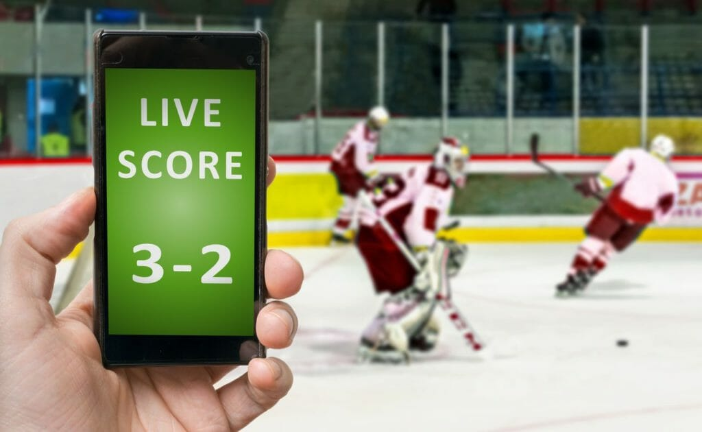 Live score online betting on a mobile phone app with ice hockey players blurred in the background