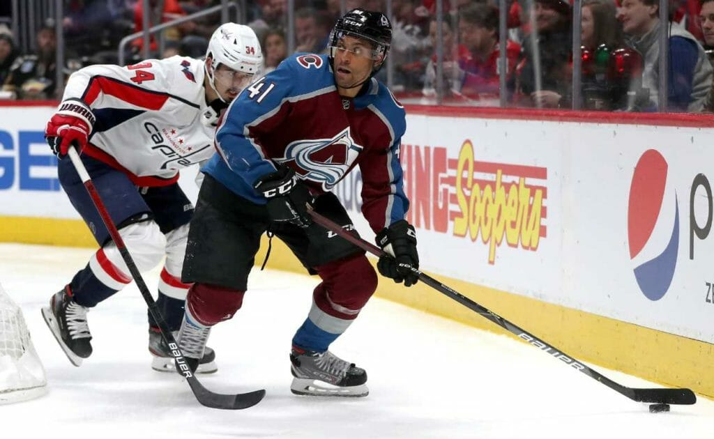 Pierre-Edouard Bellemare #41 of the Colorado Avalanche brings the puck off the boards against Jonas Siegenthaler #34 of the Washington Capitals