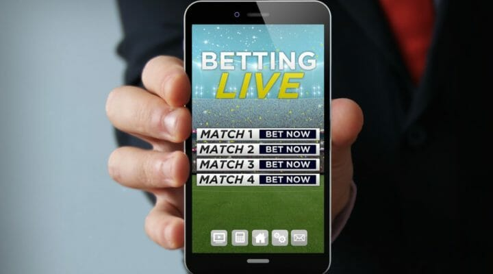 Image of a hand holding a phone with a number of matches to bet on.
