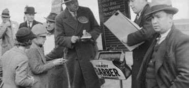 Two bookies taking bets on horse racing in 1936 with odds displayed on a blackboard
