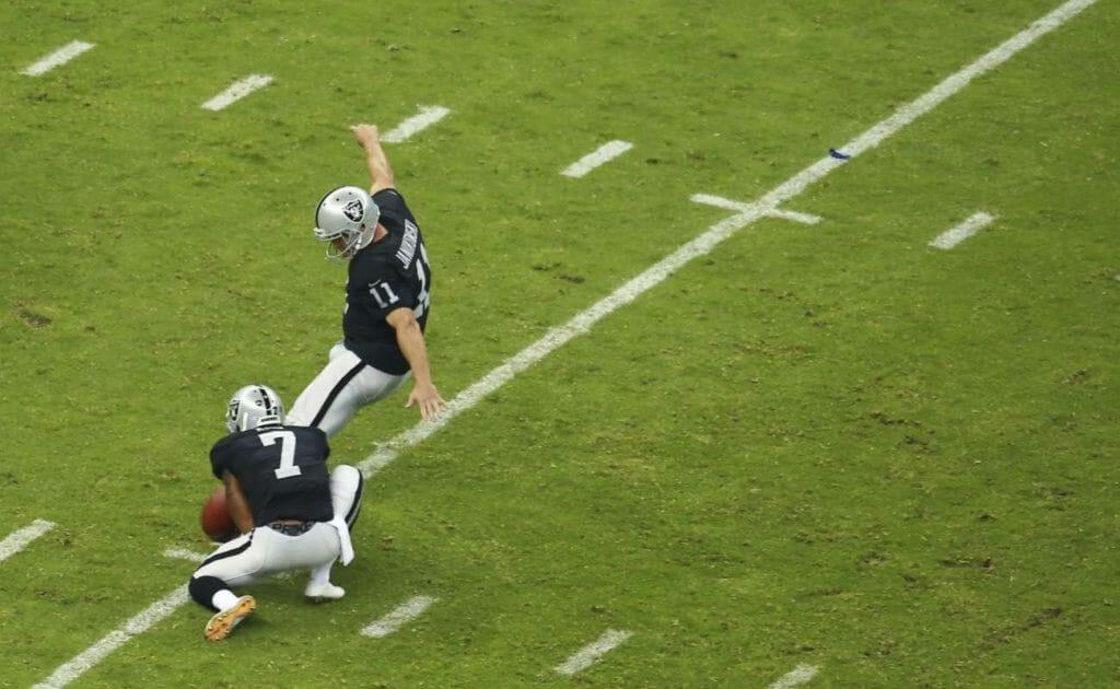 Sebastian Janikowski kicks football on the field