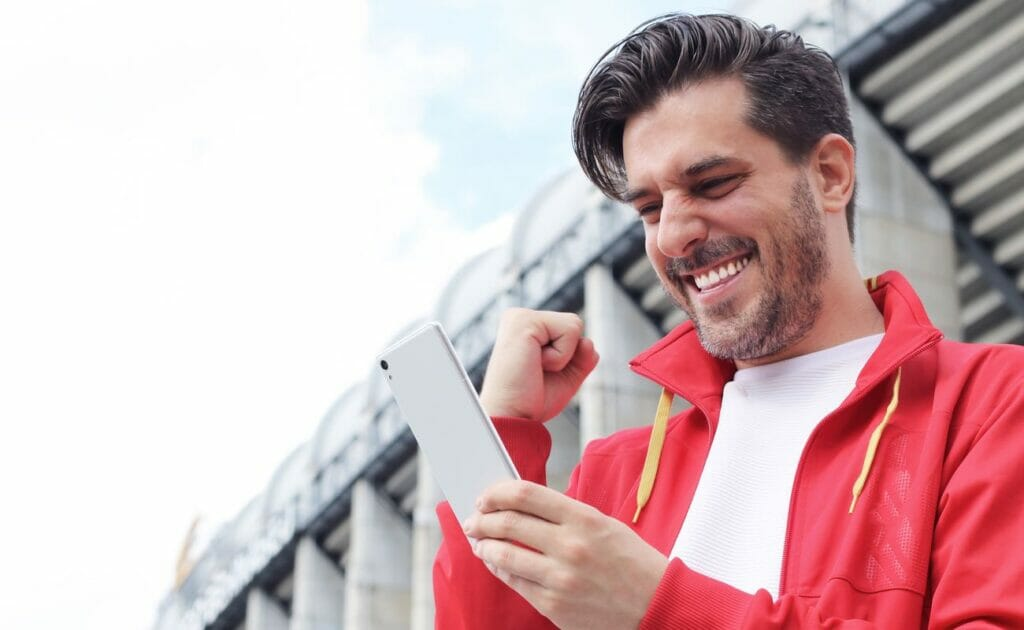 Man wearing red jacket holding smartphone celebrating online win