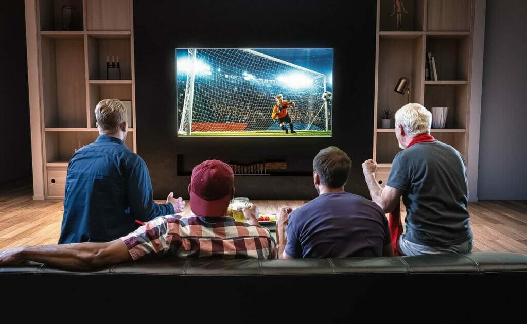 Rear view of a group of friends sitting on the couch watching soccer on a large TV screen at home