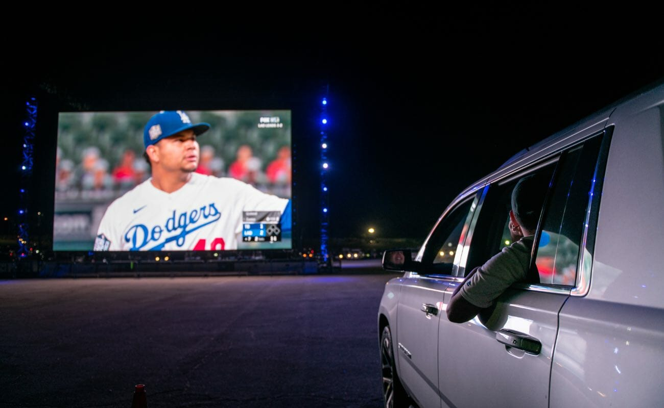 Dodgers fans watching the Los Angeles Dodgers vs. Tampa Bay Rays World Series on screen from their vehicle October, 2020 in Los Angeles, California. Photo by Brandon Bell/Getty Images