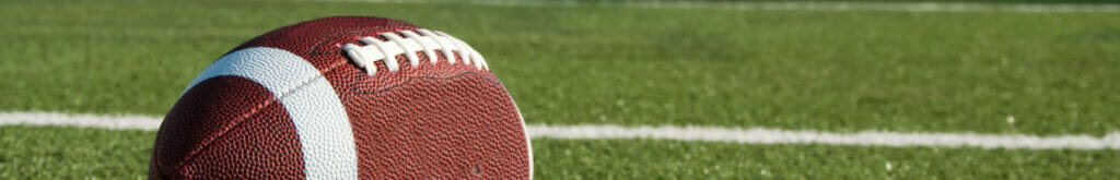 Closeup of an American football on field with goal post in background.